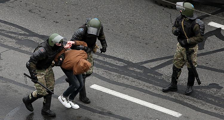 Tre poliser är på en gata. De har hjälmar på sig och masker för ansiktet. Två av poliserna har tagit fast en person.