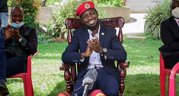 Bobi Wine sitter på en stol i sin trädgård. Han ler. Han har en röd basker på sig. På bordet framför honom ligger mikrofoner.