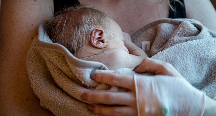 ett nyfött barn i en famn.