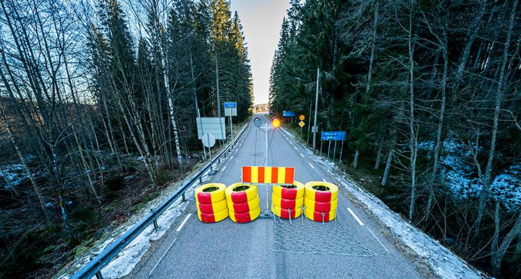 Bilden visar en väg för bilar. Vägen är spärrad med däck. Däcken är målade i rött och gult.