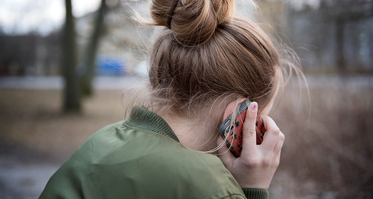 Ett barn håller i en telefon mot örat. Hon sitter utomhus.