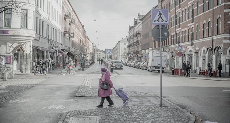 En kvinna med en väska på hjul går över ett övergångsställe i ett grått Malmö