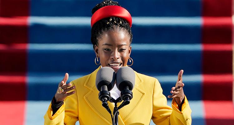 Hon är svart. Hon har gul kavaj och rött band i håret.