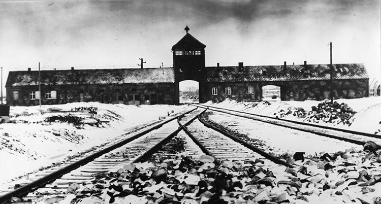 En svartvit bild där järnvägsräls ses i förgrunden och leder mot en stor tegelbyggnad med en tornliknande öppning in.