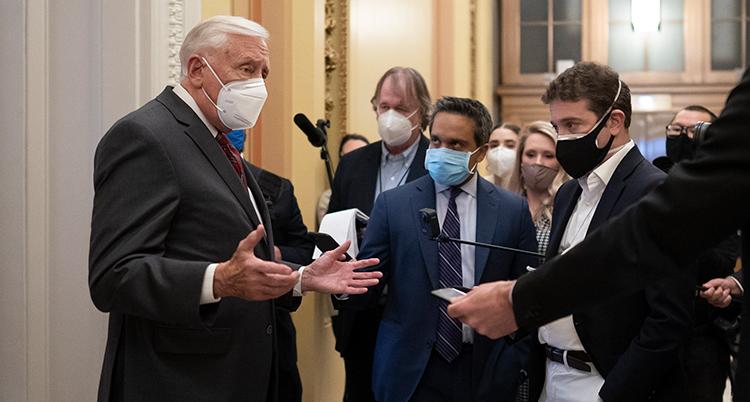 En man i kostym med munskydd står framför en grupp journalister. Han slår ut med händerna. Några journalister sträcker fram mikrofoner.