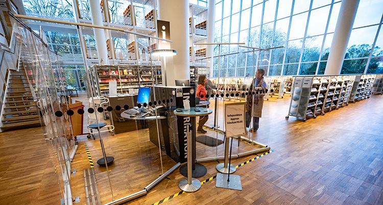 En glasbur i biblioteket. Inne i buren jobbar folk med information om biblioteket.