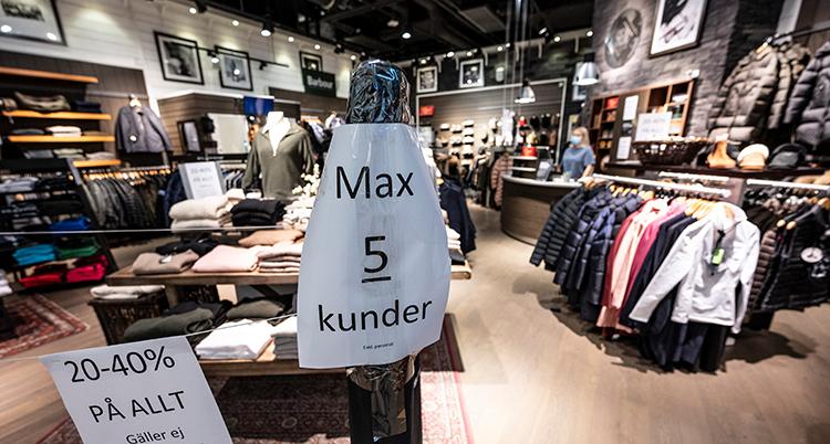En butik med hyllor och rack med kläder. En skylt säger att bara fem får vara i butiken. Butiken är tom på människor.