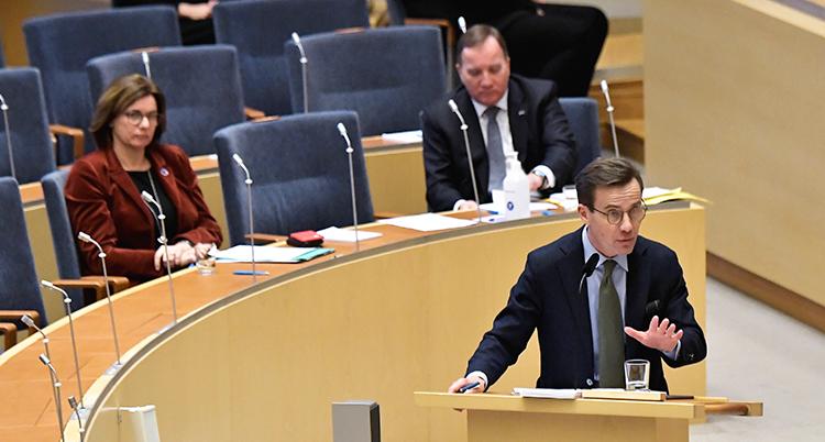 Krister står i talarstolen och talar. I bankar bakom sitter Isabella Lövin och Stefan Löfven. De ser allvarliga ut.