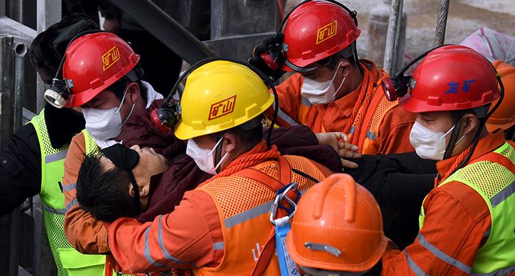 Räddningsarbetare i hjälmar bär en man med svart ögonskydd.