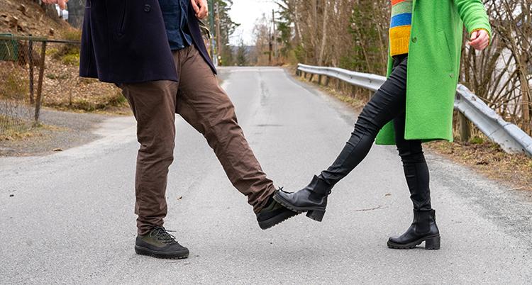 Två personer nuddar varandras fötter. De är utomhus och har skor på sig.