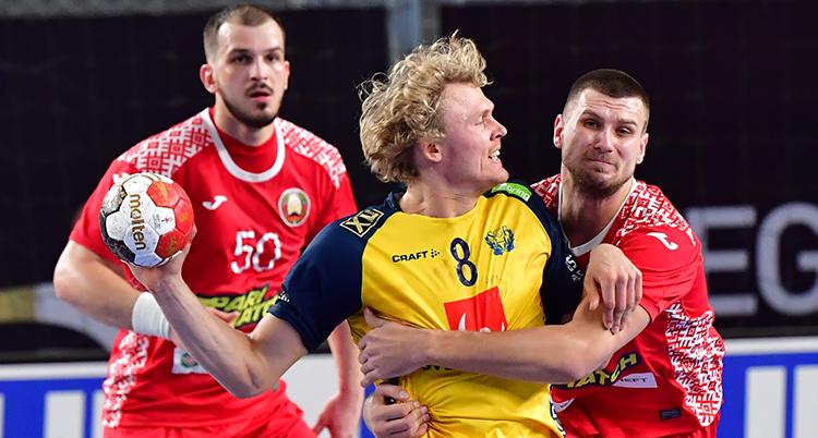 En svensk spelare med bollen stoppas av två belaruser.