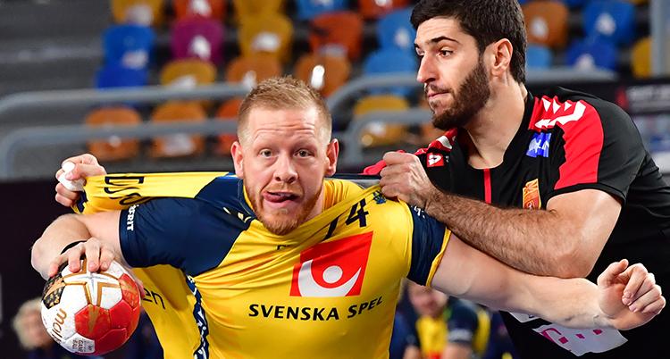 En svensk är på väg förbi en försvarare. Försvararen har tagit tagit tag i hans tröja. det ser ut som om den ska gå sönder. Svensken har bollen och har en koncentrerad blick rakt fram.
