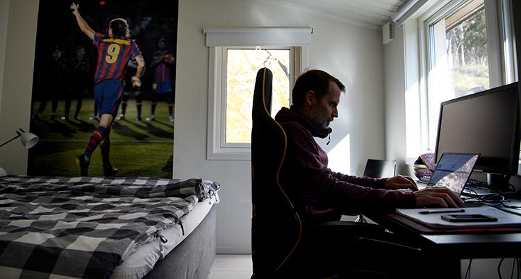 Han sitter i en ergonomisk kontorsstol vid ett skrivbord i ett sovrum, intill fönster.