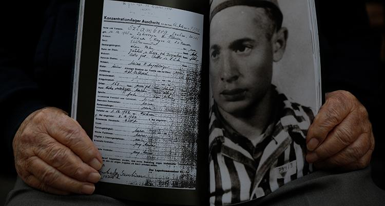 Två händer håller en svartvit bild på en man i randiga kläder. På andra sidan bilden syns en sida med text.