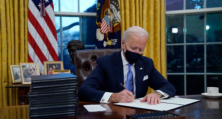 Han sitter vid ett skrivbord. Han har munskydd. Han skriver på ett papper.