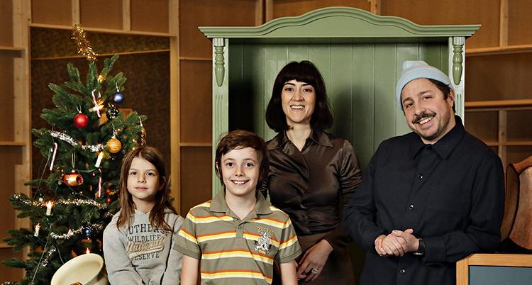 Två vuxna och två barn står bredvid varandra och ler.