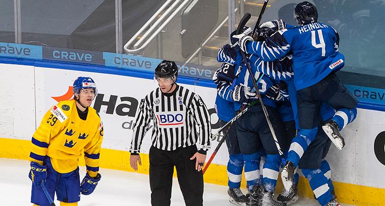 En ledsen svensk spelar står på isen. Bakom honom firar en grupp finländare sitt mål.