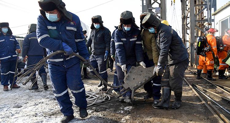 Räddningsarbetare i arbetskläder och munskydd drar en stor metallbit
