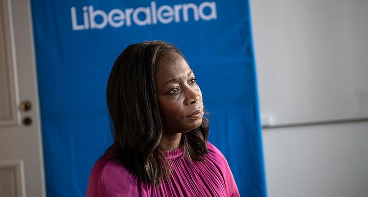 Sabuni i närbild från. Hon ser ledsen ut. Bakom henne står det Liberalerna på väggen.