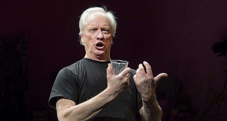 Han håller ett glas vatten i höger hand och formar läpparna i sång.