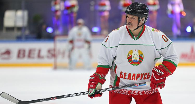 Ledaren håller i en klubba. Han har ishockeykläder på sig.