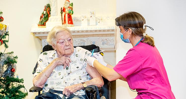 En sjuksköterska i rosa kläder och visir ger en spruta i armen på en kvinna som sitter i rullstol.