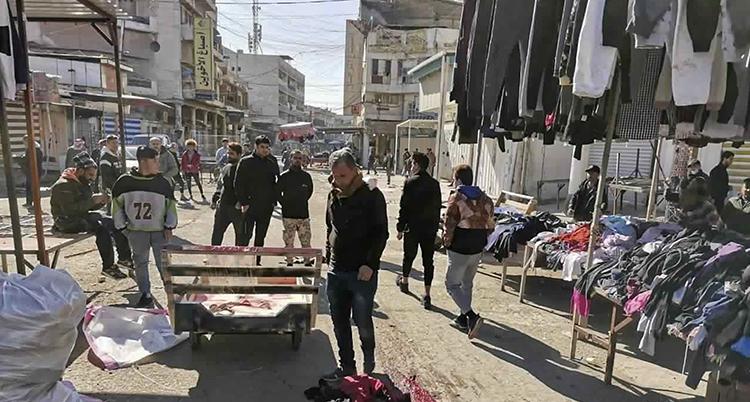 Blod syns på marken. Många kläder hänger längs gatan.