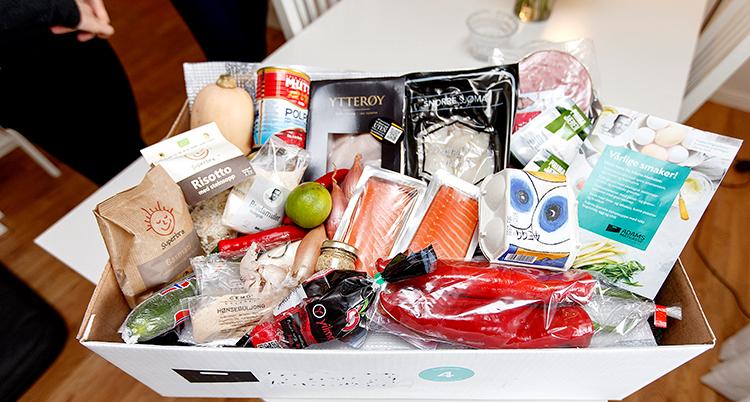 En låda full med mat. Bland annat lax, paprika, gurka och risotto.