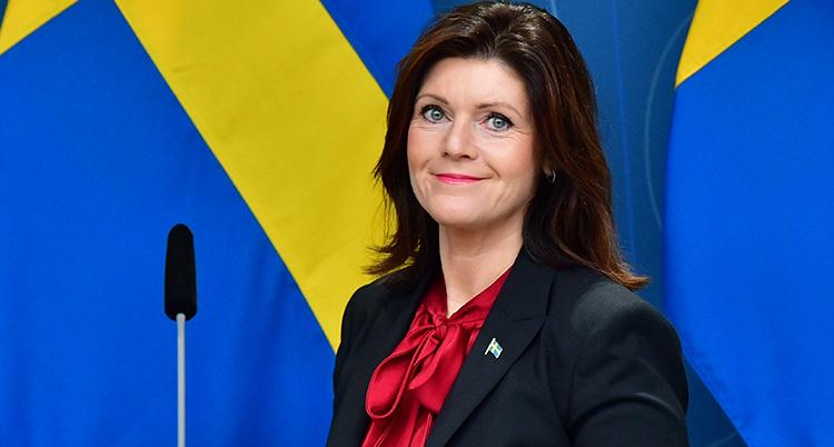 Hon står framför en svenska flagga med en mikrofon bredvid sig. Hon ler och tittar in i kameran.