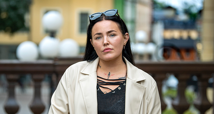 Hon har ljus jacka och svart tröja, svart långt hår och tittar in i kameran