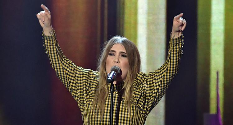 Hon står vid en mikrofon och sjunger, bär en guloch svartaktig överdel och sträcker båda händerna i luften.