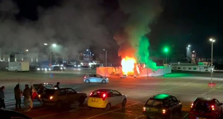 Ett litet hus brinner på en stor parkeringsplats.