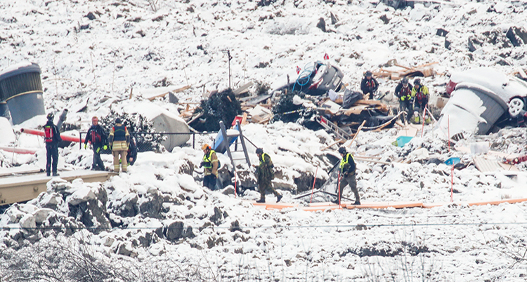 Räddningsarbetare jobbar i snöiga jordmassor