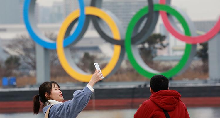 Två personer framför stora olympiska ringar. De tar bilder av sig själva.