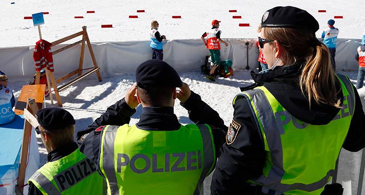 Tre poliser med gula västar tittar på skidspår.