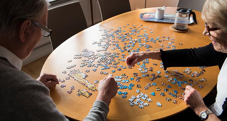 Ett matbord där en man och en kvinna lägger ett pussel med många bitar.