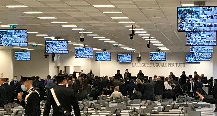 Många poliser och skrivbord syns. I taket hänger tv-skärmar.