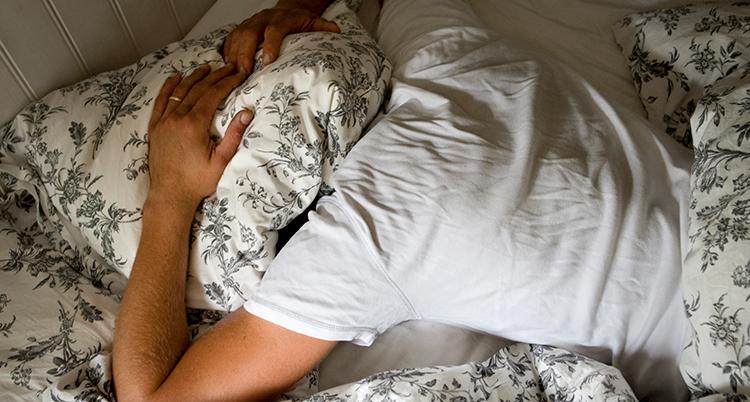 En man ligger i en säng. Han har huvudet under kudden.