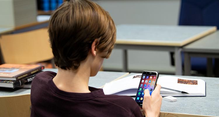 En elev sitter i en skolbänk, med ryggen mot kameran, och tittar i sin mobil. På bänken ligger skolböcker.