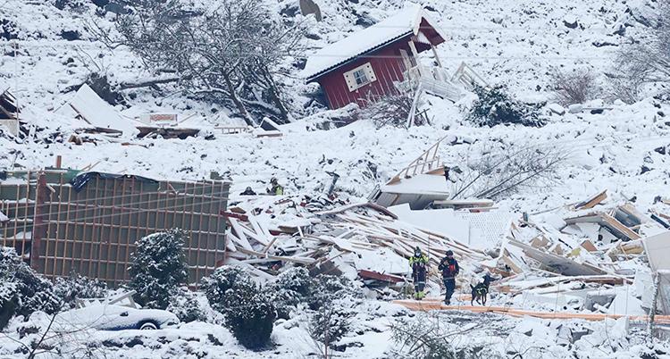 Ett rött hus syns i den snöiga raskanten. Räddningsarbetare går i det snöiga rasområdet.