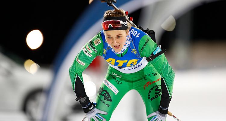 Stina Nilsson har grön dräkt. Hon har precis gått i mål. Hon lutar sig på knäna och ser trött ut.