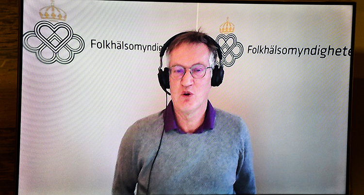 En filmad bild när han står och berättar. Han har hörlurar med en mikrofon på sig.