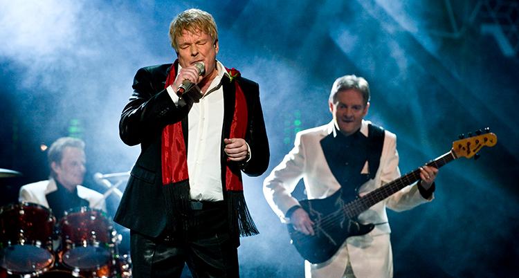 Thorleif Torstensson är klädd i en kostym och vit skjorta och en röd halsduk. Han blundar och sjunger i en mikrofon.