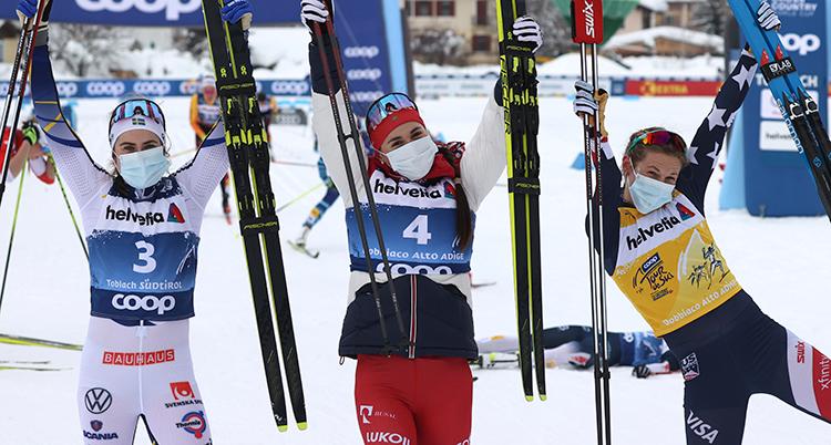 Tre skidåkare med munskytt. De håller upp skidor och stavar i och ser glada ut. Till höger är Diggins. Hon gör en konstig rörelse och sträcker ut benet.