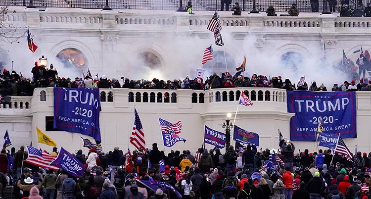 Många människor trängs framför riksdagen. De har banderoller och flaggor där det står Trump.
