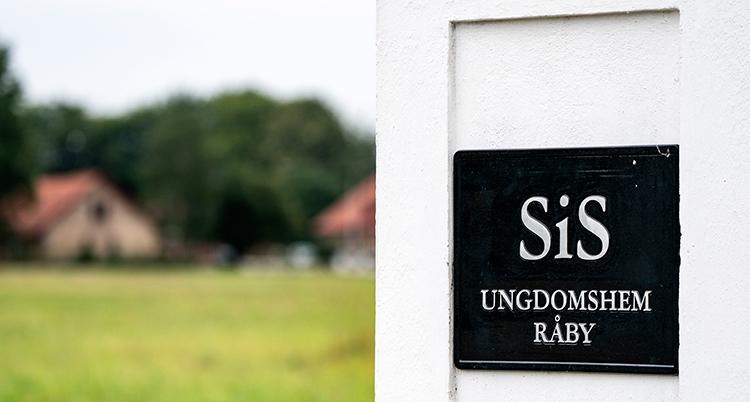 En skylt visar att det är ett ungdomshem, bortom ett grönt fält syns ett gult hus