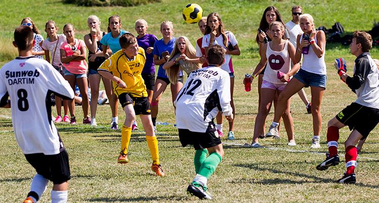 Många unga i fotbollströjor olika färger är på en fotbollsplan.