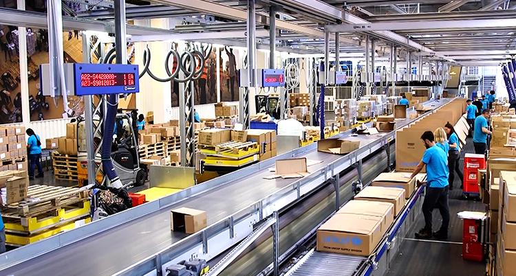 Bruna kartonger åker fram på ett löpande band i ett stort lager där människor jobbar