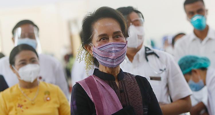 Aung San Suu Kyi gör ett besök hos personal som jobbar med sjukvård och viruset corona. Flera i personalen står runt henne med munskydd. Aung San Suu Kyi har också ett munskydd som är lila.