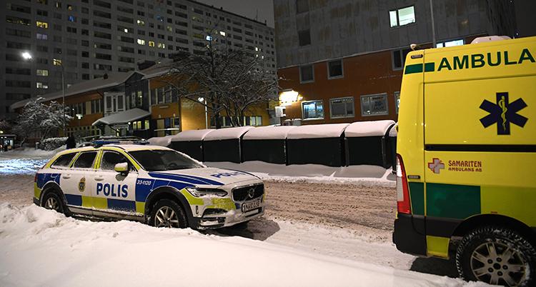 En polis och en ambulans parkerade på en gata i ett bostadsområde.